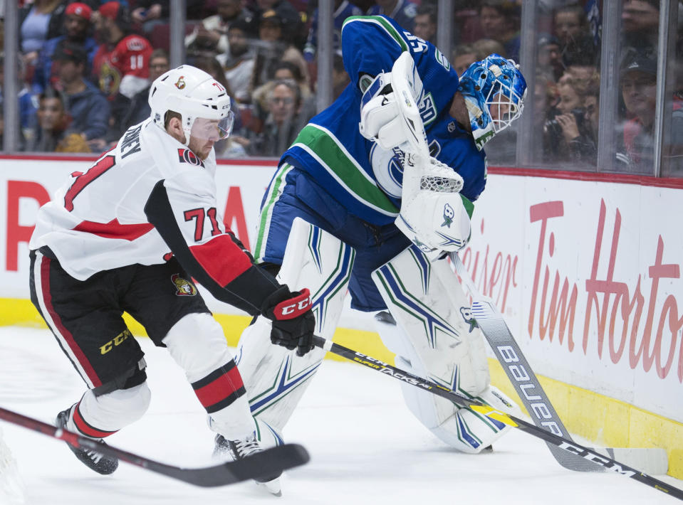 Ottawa Senators center Chris Tierney (71) tries to get the puck from Vancouver Canucks goaltender Thatcher Demko (35) during the third period of an NHL hockey game Tuesday, Dec. 3, 2019, in Vancouver, British Columbia. (Jonathan Hayward/The Canadian Press via AP)