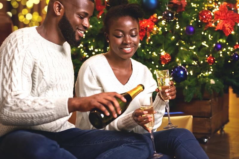 Happy african american couple toasting New Year's Eve, celebrating winter holidays at home together.