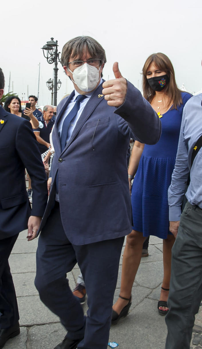 Catalan separatist leader Carles Puigdemont, left, gives thumbs up as he walks with the Speaker of the Catalan Parliament Laura Borras in Alghero, Sardinia, Italy, Saturday, Sept. 25, 2021. Puigdemont took a leisurely walk in the Sardinian city, waving to supporters, a day after a judge freed him from jail pending a hearing on his extradition to Spain, where the political firebrand is wanted for sedition. (AP Photo/Francesca Salaris)