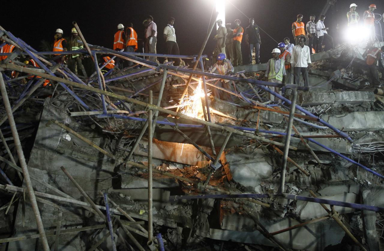 Rescue workers conduct a search operation for survivors at the site of a collapsed 11-storey building that was under construction on the outskirts of the southern Indian city of Chennai June 28, 2014. Two building collapses in New Delhi and Tamil Nadu states killed at least 11 people on Saturday and left dozens trapped, highlighting the need for increased monitoring of construction across India where such incidents are common. REUTERS/Babu (INDIA - Tags: DISASTER)