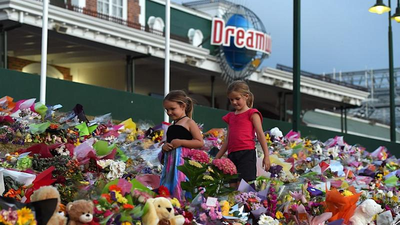 Young girls walk through a floral tribute outside the Dreamworld Theme Park on the Gold Coast. Photo: AAP