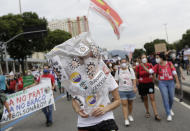 A woman wears a plastic bag decorated with stickers depicting Brazilian President Jair Bolsonaro as a virus, during a demonstration against Bolsonaro's handling of the coronavirus pandemic and economic policies protesters say harm the interests of the poor and working class, in Rio de Janeiro, Brazil, Saturday, June 19, 2021. Brazil is approaching an official COVID-19 death toll of 500,000 — second-highest in the world. (AP Photo/Bruna Prado)