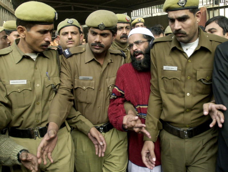 FILE - In this Dec. 17, 2002 file photo, Mohammad Afzal Guru, second from right, a Kashmiri man convicted of involvement in a 2001 attack on India's Parliament, is produced at a court in New Delhi, India. For 11 years the family of the convicted terrorist waited and wondered about his fate as he sat on death row. Two weeks ago they found out — from television. Guru had been hanged in secrecy in a faraway jail in New Delhi. A government letter informing them of the imminent hanging arrived at their home in Kashmir two days after he was dead. (AP Photo/Aman Sharma, File)