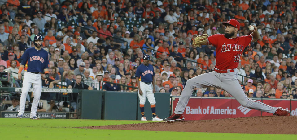 Los Angeles Angels pitcher Williams Jerez, right, strikes out Houston Astros' Martin Maldonado to retire the side with Astros' Marwin Gonzalez on third and the bases loaded in the seventh inning of a baseball game Sunday, Sept. 23, 2018, in Houston. (AP Photo/Richard Carson)