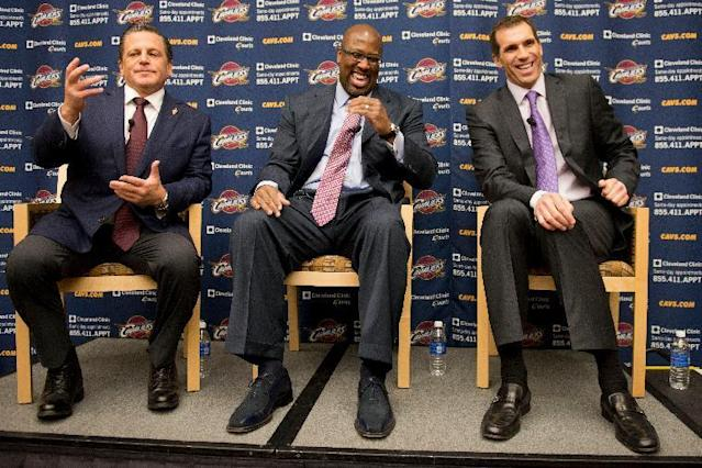 FILE - In this April 24, 2013 file photo, Cleveland Cavaliers owner Dan Gilbert, left, gestures as new head coach Mike Brown, center, and general manager Chris Grant laugh during an NBA basketball news conference in Independence, Ohio.The flailing Cavaliers fired general manager Chris Grant, Thursday, Feb. 6, 2014. With the Cavs sliding further toward the bottom in another disappointing season, owner Dan Gilbert decided to make the move a day after Cleveland was beaten Wednesday night by an injury-ravaged Los Angeles Lakers team that finished the game with just five players. (AP Photo/Jason Miller)