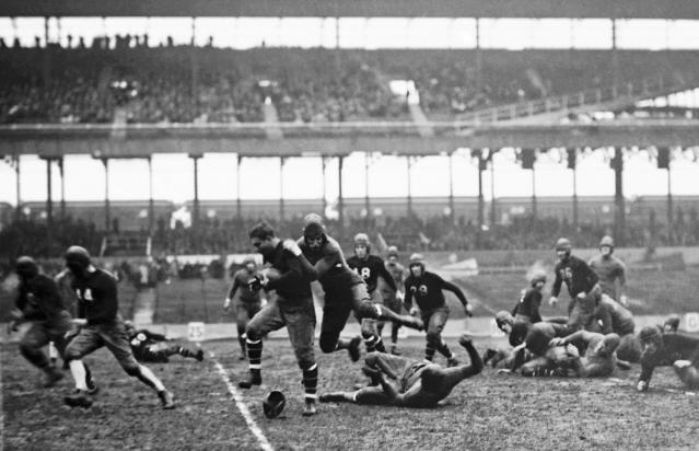 FILE - In this Nov. 24, 1929, file photo, New York Giant's Benjamin Friedman is stopped after making a 10-yard gain against the Green Bay Packers during a football game at the Polo Grounds in New York City. The first season, 1920, the American Professional Football Association had 14 teams. Throughout a decade of flux, many franchises came and went.(AP Photo/File)