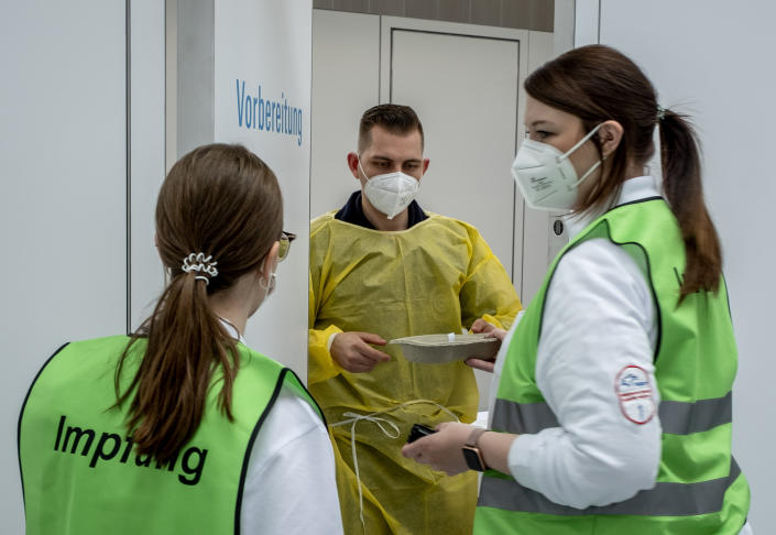 """A laboratory worker talks to a vaccination doctors as Fraport airport company vaccinates their employees in a gym at the airport in Frankfurt, Germany, Friday, April 30, 2021. Letters on back read """"vaccination"""". (AP Photo/Michael Probst)"""