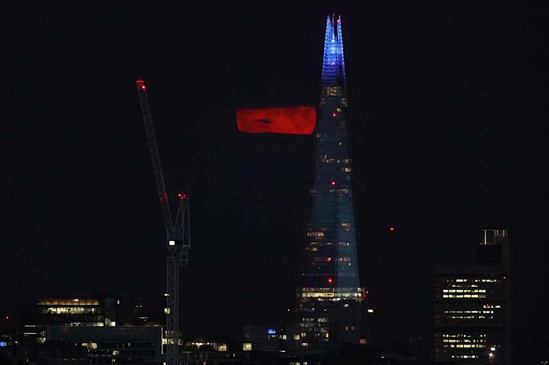 A full Moon, known as the Sturgeon Moon, is partially seen from behind clouds over the Shard building in London (PA)