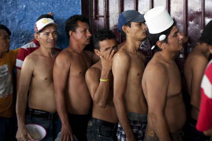 In this May 3, 2012 photo, inmates wait in line for lunch in San Pedro Sula Central Corrections Facility in San Pedro Sula, Honduras. Inside one of Honduras' most dangerous and overcrowded prisons, inmates operate a free-market bazaar, selling everything from iPhones to prostitutes. Guards do not cross into the inner sanctum controlled by prisoners, and prisoners do not breach the perimeter controlled by guards. (AP Photo/Rodrigo Abd)