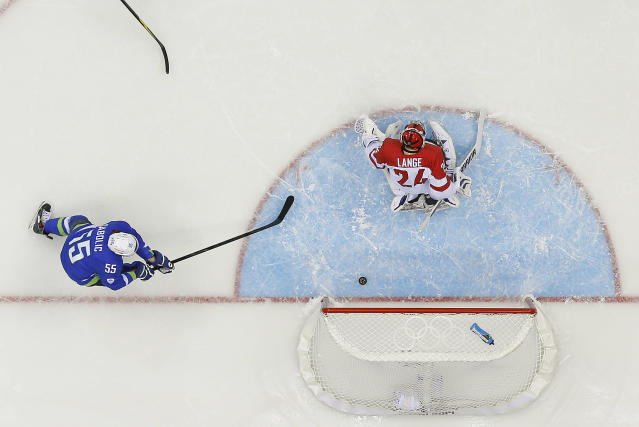 The puck, shot by Slovenia forward Anze Kopitar slips past Austria goaltender Mathias Lange for a goal as Slovenia forward Robert Sabolic looks to assist in the first period of a men's ice hockey game at the 2014 Winter Olympics, Tuesday, Feb. 18, 2014, in Sochi, Russia. (AP Photo/David J. Phillip )