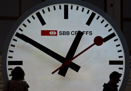 Visitors are silhouetted against a giant railway clock at the Swiss railway
