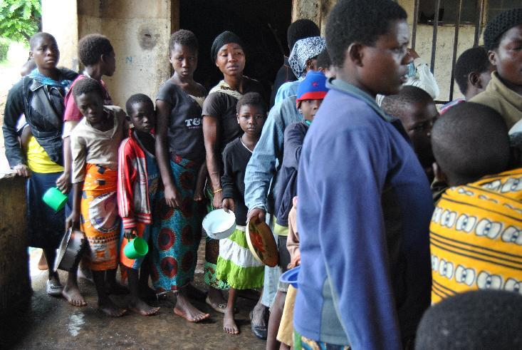 Malawian people left homeless due to heavy rains queue for food at Chimwankhunda primary school in Blantyre on January 15, 2015 (AFP Photo/Bonex Julius )
