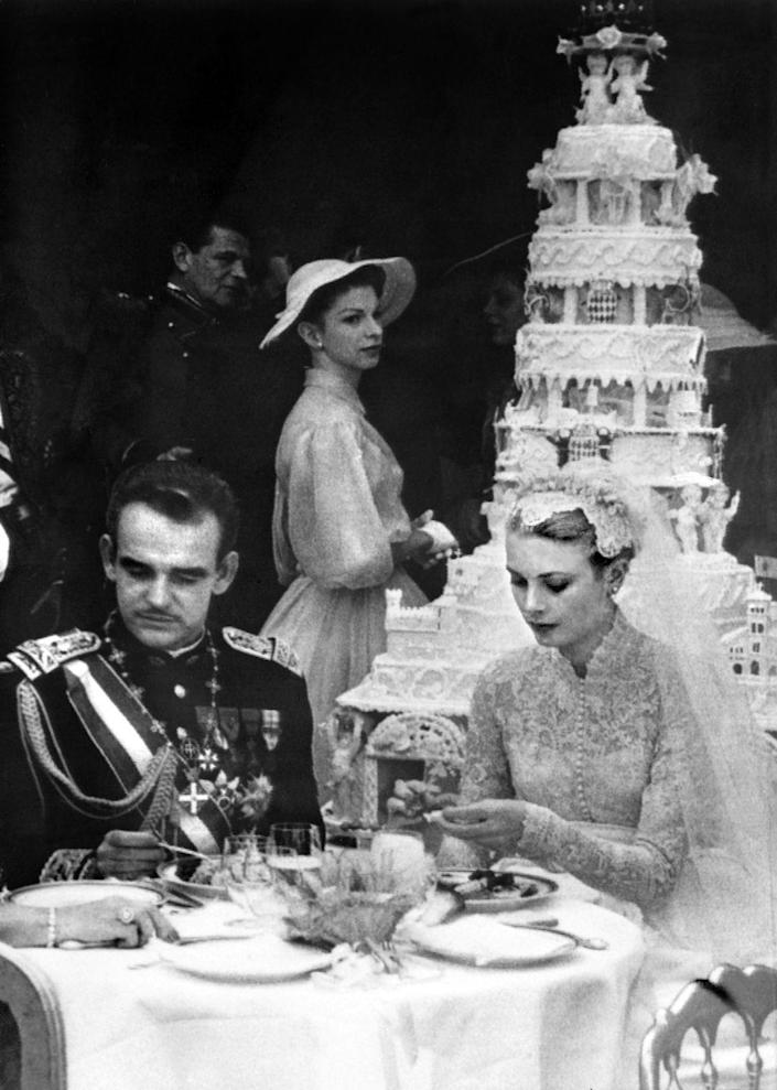 <p>After their religious ceremony, Princess Grace and Prince Rainier enjoy a wedding lunch. The bride wears her iconic lace collared wedding dress and headpiece veil, and the couple sits in front of their elaborate multitiered wedding cake. </p>