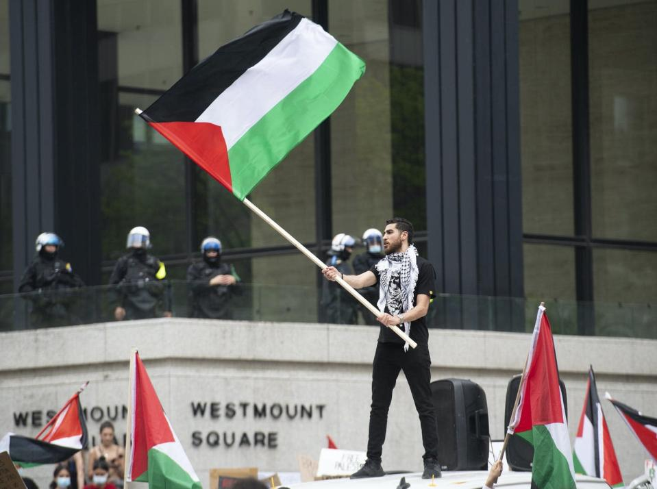 A man wearing a Keffiyeh around his neck stands above a crowd waving a Palestinian flag. Police officers stand in the background.