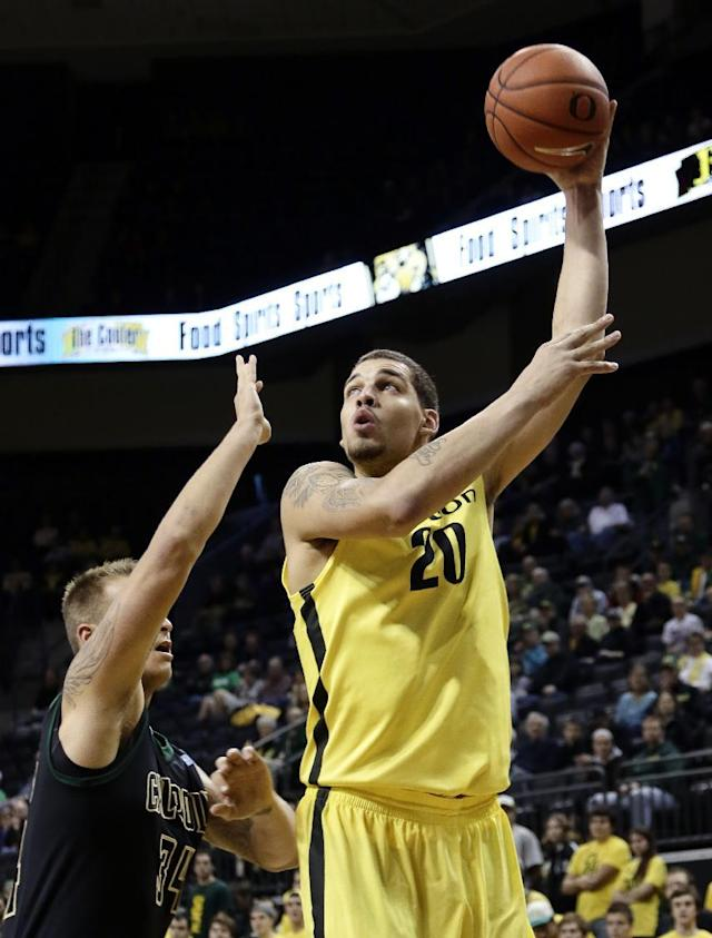 Oregon center Waverly Austin, right, shoots over Cal Poly forward Brian Bennett during the first half of an NCAA college basketball game in Eugene, Ore., Sunday, Dec. 1, 2013. (AP Photo/Don Ryan)