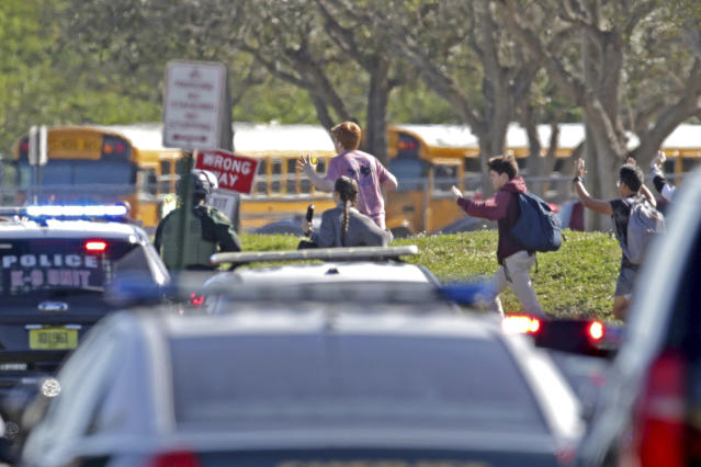 <p>Students run with their hands in the air following a shooting at Marjory Stoneman Douglas High School in Parkland, Fla., on Feb. 14, 2018. (Photo: John McCall/South Florida Sun-Sentinel via AP) </p>