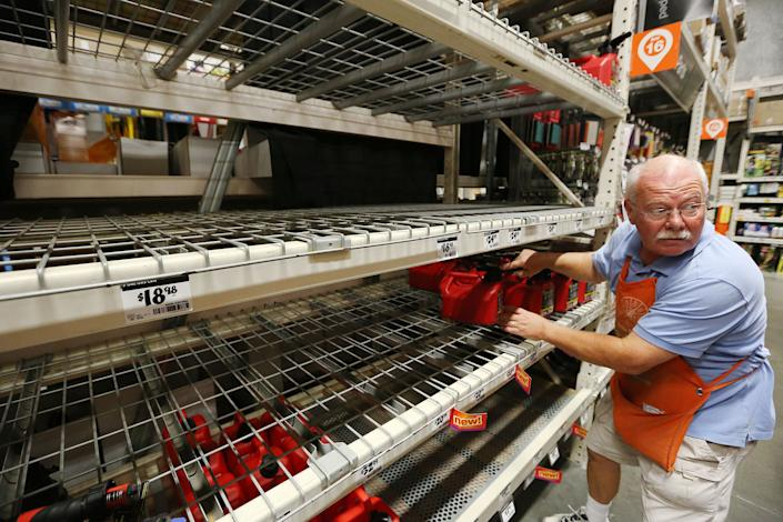 Ed Fluker arranges the last remaining gas containers on otherwise empty shelves at The Home Depot in Lady Lake, Florida.