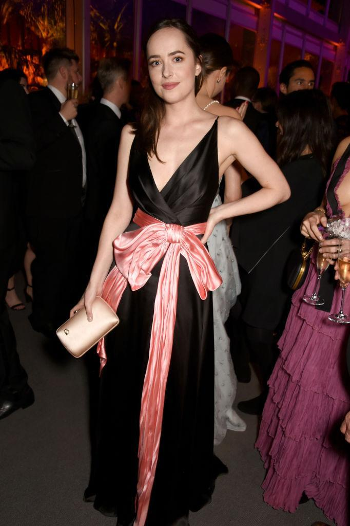 <p>Take a close look at Dakota Johnson's clutch – and spot the Planned Parenthood pin. (Photo: Getty Images) </p>