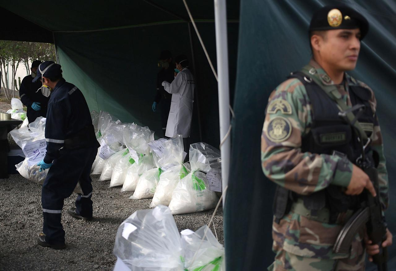 <p>A police officer stands guard while two workers carry a bag of seized cocaine to be destroyed by fire at a police base in Lima, Peru, Tuesday, Oct. 11, 2016. Police say they will burn more than 7 tons of drugs on Tuesday, including cocaine, marijuana, opium and heroin that was seized over the last four months. (AP Photo/Martin Mejia) </p>