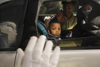 A young boy watches as a reflected, social distant Santa waves while visiting Santa's Garage on top of a parking deck near Soldier Field in Chicago on Dec. 10, 2020. In this socially distant holiday season, Santa Claus is still coming to towns (and shopping malls) across America but with a few 2020 rules in effect. (AP Photo/Charles Rex Arbogast)