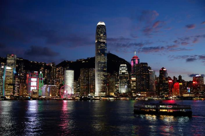 FILE PHOTO: A Star Ferry boat crosses Victoria Harbour in front of a skyline of buildings during sunset.