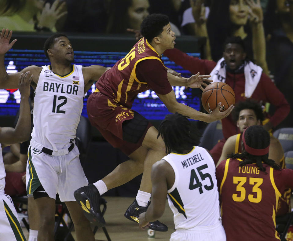 Iowa State guard Rasir Bolton (45) attempts a shot between Baylor guard Jared Butler (12) and Baylor guard Davion Mitchell (45) in the second half of an NCAA college basketball game, Tuesday, Feb. 23, 2021, in Waco, Texas. (AP Photo/Jerry Larson)