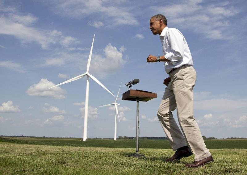 As wind turbines turn on the distance, President Barack Obama changes direction as he walks from a podium after speaking at the Heil family farm , Tuesday, Aug. 14, 2012, in Haverhill, Iowa, during a three day campaign bus tour through Iowa. (AP Photo/Carolyn Kaster)