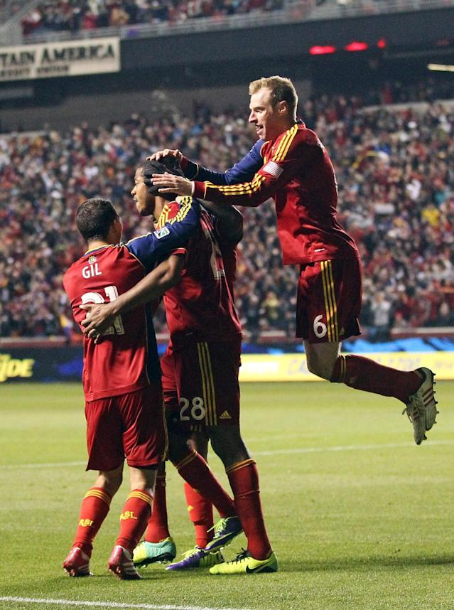 Real Salt Lake midfielder Luis Gil (21) and teammate Real Salt Lake defender Nat Borchers (6) celebrate with Chris Schuler (28) after scoring against the Portland Timbers in the first half during the first leg of the MLS Western Conference final Sunday, Nov. 10, 2013, in Sandy, Utah. (AP Photo/Rick Bowmer)
