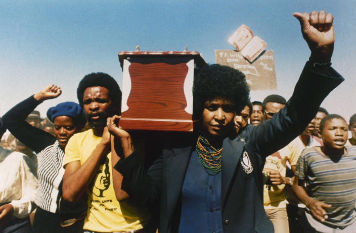 <p>Winnie Mandela, black activist and wife of jailed South African National Congress leader Nelson Mandela, carries the coffin of William Kotoyi at his funeral in Brandfort, South Africa, on April 5, 1986. In a speech there, she called for full sanctions against South Africa for its apartheid policies. (Photo: AP) </p>