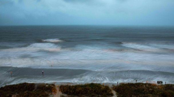 PHOTO: Large surf is swirled by the wind and captured by a long exposure, while a person stands on the shore as Hurricane Isaias approaches North Myrtle Beach, SC on August 3, 2020.  (Logan Cyrus/AFP via Getty Images)