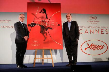 Cannes Film festival general delegate Thierry Fremaux and Cannes Film festival president Pierre Lescure pose in front of the official poster for the 70th Cannes Film Festival after a news conference in Paris