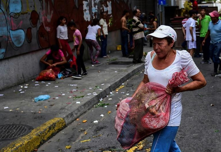 People collect vegetables after a street market was looted in the Chacao neighborhood of Caracas on March 10, 2019 -- the third full day of a massive blackout paralyzing Venezuela