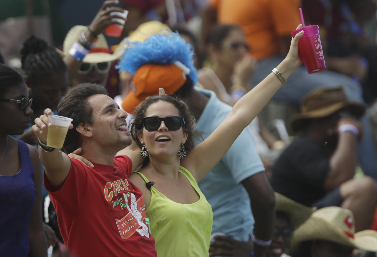 Fans cheer during a one-day international cricket match between England and West Indies at the Sir Vivian Richards Cricket Ground in St. John's, Antigua, Friday, Feb. 28, 2014. (AP Photo/Ricardo Mazalan)