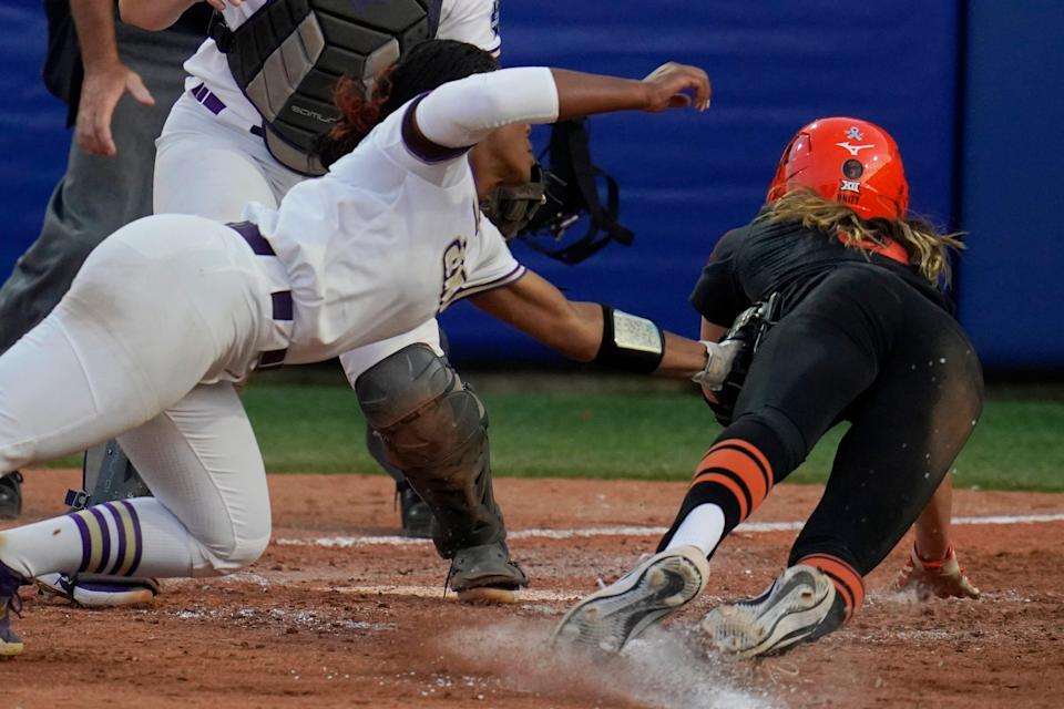 Oklahoma State's Scotland David, right, is tagged out at home plate by James Madison pitcher Odicci Alexander, left, in the seventh inning.