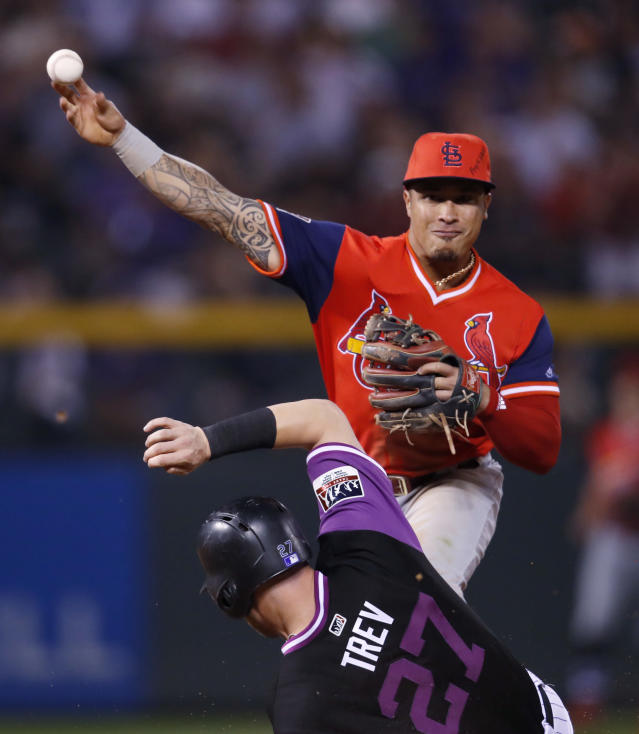 St. Louis Cardinals second baseman Kolten Wong, top, throws over Colorado Rockies' Trevor Story after forcing him out at second base on a ground ball hit by Ian Desmond in the fifth inning of a baseball game Friday, Aug. 24, 2018, in Denver. (AP Photo/David Zalubowski)