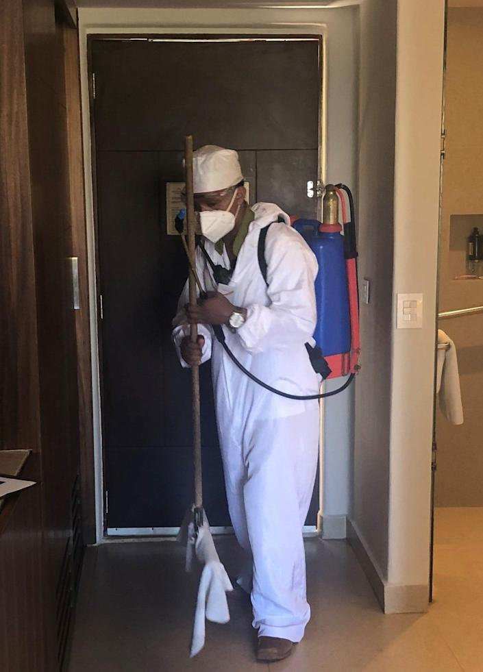 An employee at the Fiesta Americana Condesa Cancun, an all-inclusive resort in Mexico, sanitizes a guest room.