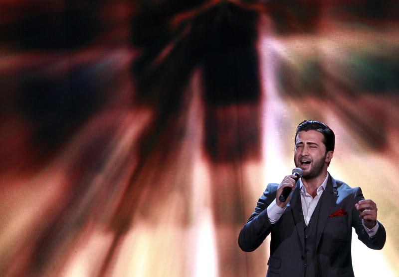 In this Friday, April 26, 2013 photo, Syrian singer Abdel Karim Hamdan, performs during the Arab Idol Show broadcast by MBC Arabic satellite channel, in Zouk Mosbeh neighborhood, north of Beirut, Lebanon. Hamdan, a 25-year-old music student, who comes from a large, traditional and poor Muslim family in Aleppo, put himself through school by working by working at gas stations and constructions sites. He was determined to succeed, and neither fighting nor criticism from both sides of Syria's civil war was going to ruin his chance to let the Arab world hear him sing. (AP Photo/Bilal Hussein)