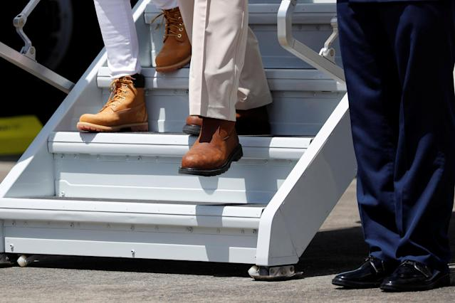 <p>President Donald Trump and first lady Melania Trump (L), wearing boots, arrive aboard Air Force One, to survey hurricane damage, at Muniz Air National Guard Base in Carolina, Puerto Rico, Oct. 3, 2017. (Photo: Jonathan Ernst/Reuters) </p>
