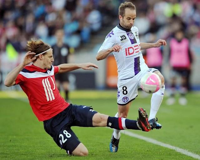 Toulouse's French midfielder Didot Etienne (R) vies with Lille's Argentinian defender Mauro Cetto during the French L1 football match Lille vs Toulouse, on April 01 2012 at Lille metropole stadium in Villeneuve d'Ascq, northern France. AFP PHOTO / PHILIPPE HUGUEN