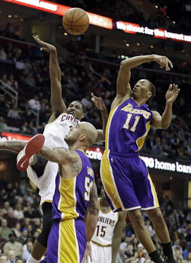 Cleveland Cavaliers' Tristan Thompson, back, loses control against the Memphis Grizzlies Los Angeles Lakers' Wesley Johnson (11) and Robert Sacre (50) in the first quarter of an NBA basketball game on Wednesday, Feb. 5, 2014, in Cleveland. (AP Photo/Mark Duncan)