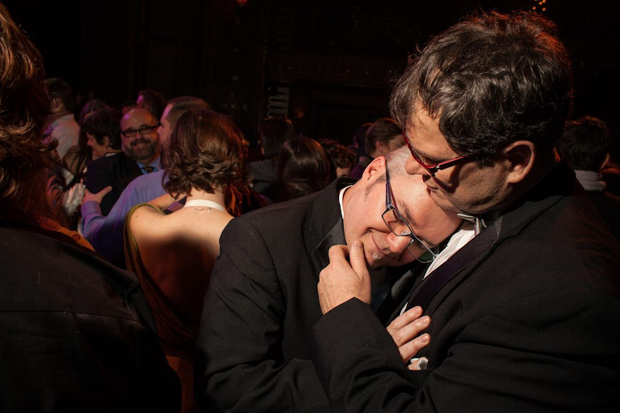 "SEATTLE, WA - DECEMBER 9: Paul Beppler (R) and his husband Terry Gilbert participate in a group first dance at ""A Wedding Reception for All,"" which was attended by hundreds and held at the Paramount Theatre on December 9, 2012 in Seattle, Washington. The two were married today after 12 years together. Today is the first day that same-sex couples can legally wed in Washington state. (Photo by David Ryder/Getty Images)"