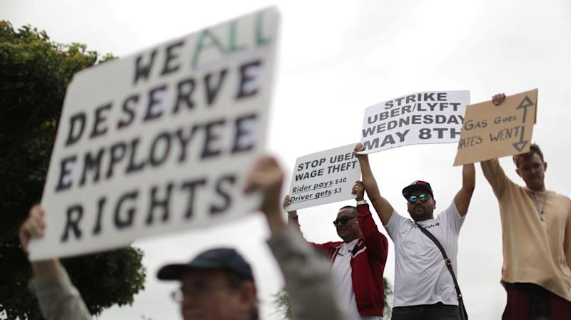 "An Uber driver holds a sign reading, ""We all deserve employee rights."""