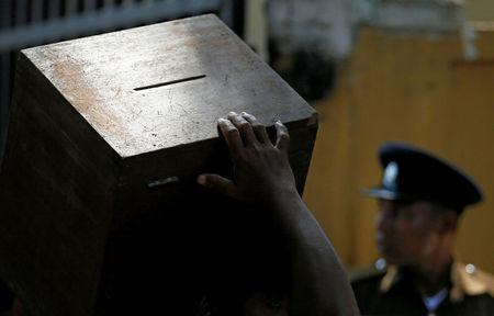 An electoral official carries a ballot box as he waits to get into a bus next to a police officer ahead of local government polls in Colombo, Sri Lanka February 9, 2018. REUTERS/Dinuka Liyanawatte