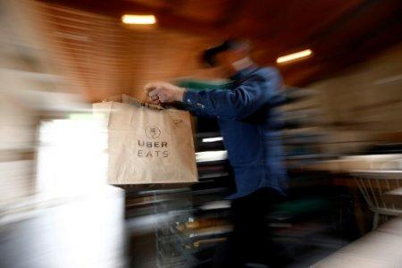 FILE PHOTO - A bag of donuts destined for delivery via Uber Eats is rushed to a driver from a kitchen in Sydney August 12, 2016. Picture taken August 12, 2016. REUTERS/Jason Reed