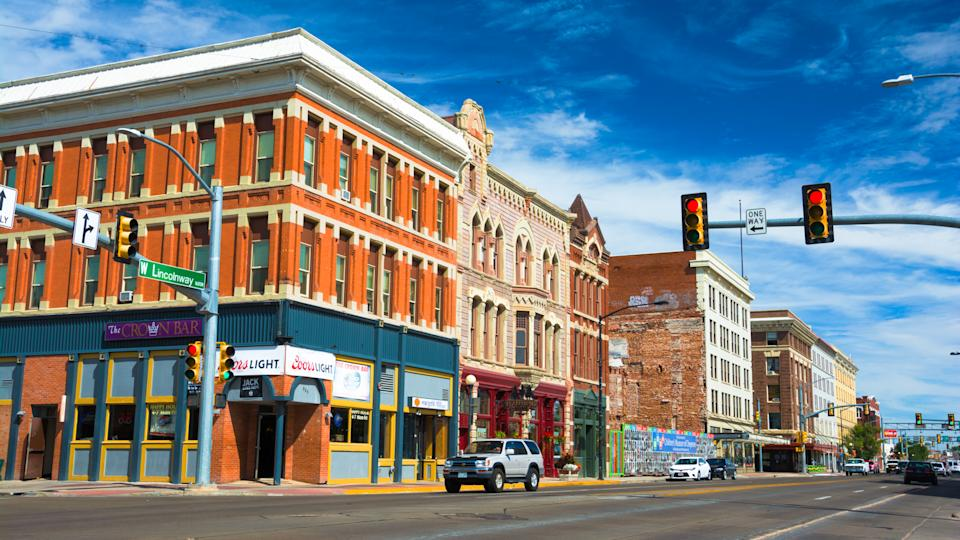 Cheyenne, United States - September 22, 2015: Downtown Cheyenne street scene with historic buildings and car with driver in an intersection.