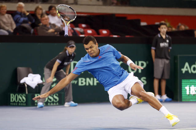 Jo Wilfried Tsonga of France falls during his first round Davis Cup tennis match against Amir Weintraub of Israel in Rouen, February 1, 2013. REUTERS/Charles Platiau (FRANCE - Tags: SPORT TENNIS) - RTR3D8BW