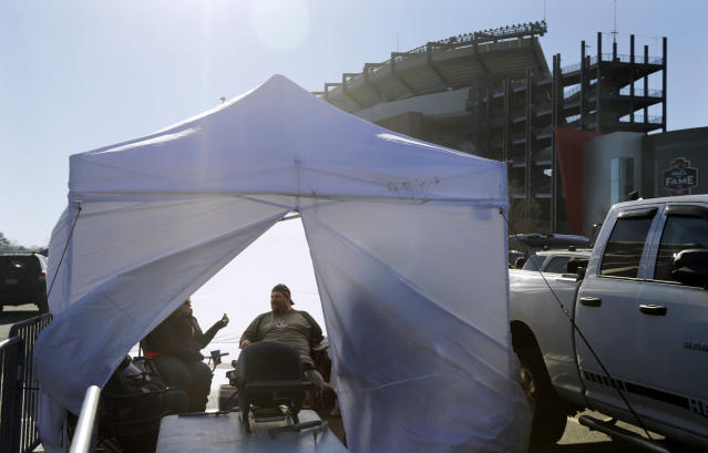 Kristi left, and Scott Garon, of Billerica, Mass., tailgate inside a tent in the parking lot of Gillette Stadium before an NFL football game between the between the New England Patriots and the Buffalo Bills, Sunday, Dec. 23, 2018, in Foxborough, Mass. (AP Photo/Elise Amendola)