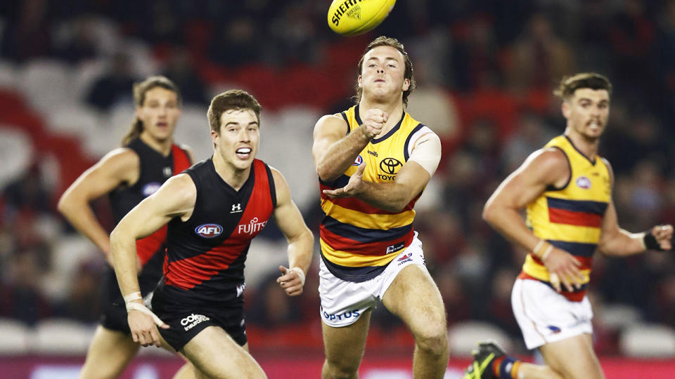 Luke Pedlar, pictured here handballing during the Adelaide Crows' clash with Essendon Bombers.