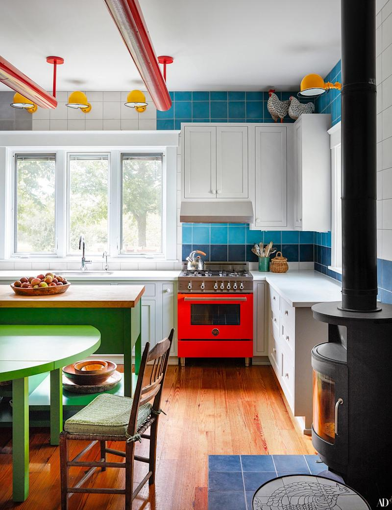 In the kitchen, custom cement tile by Mosaic House provides a serene backdrop for colorful accents. Bertazzoni range; Jieldé sconces; Rais wood-burning stove.
