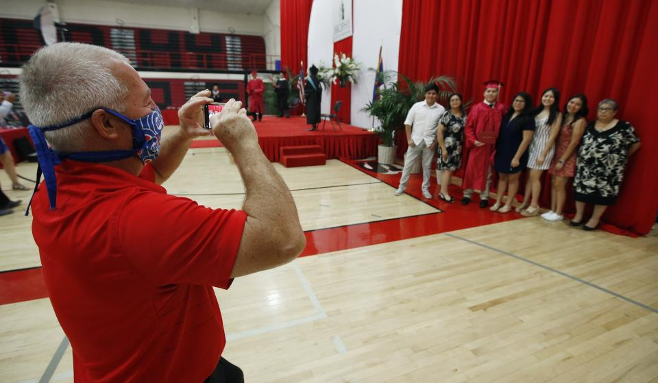 Teacher Frank Antonioli, of Brophy College Preparatory, gets a photo of a graduating senior with his family during one of several Diploma Days due to the coronavirus on May 28, 2020, in Phoenix. (AP Photo/Ross D. Franklin)